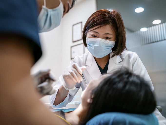 Dentist with male assistant treating female patient