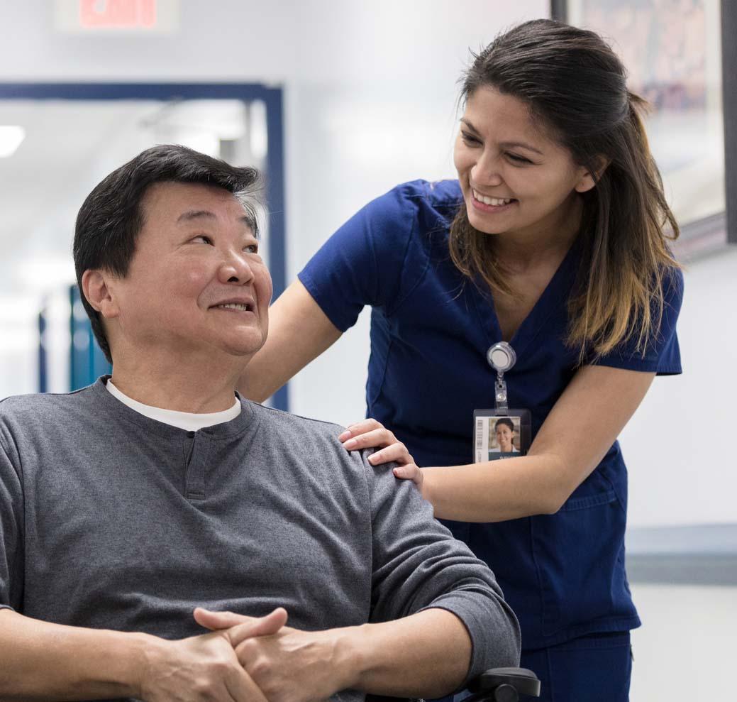 Cheerful nurse talks with senior patient