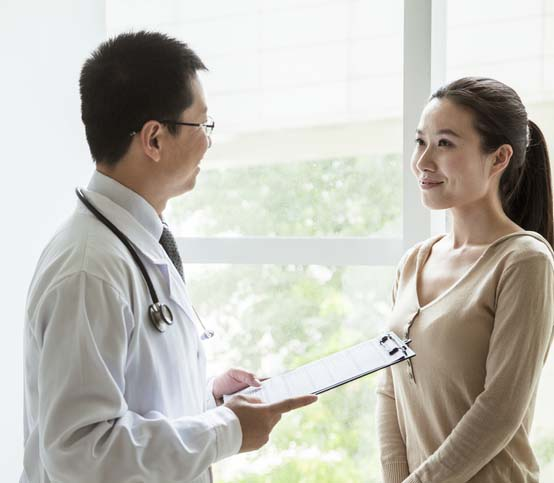 Doctor holding medical charts and discussing with a female patient in the hospital